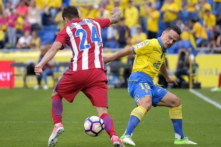 El defensa uruguayo del Atlético de Madrid José María Giménez (i) disputa un balón con el centrocampista de Las Palmas Roque Mesa. (Foto Prensa Libre: EFE)