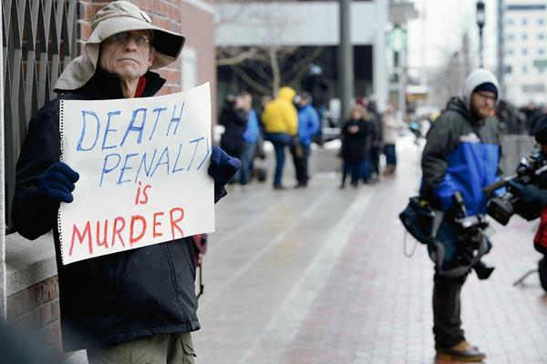 """Un ciudadano sostiene un cártel en el que se lee: """"La pena de muerte es asesinato"""", en Boston, Massachusetts, EE.UU. (Foto Prensa Libre:EFE)"""