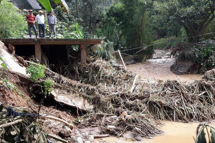 Vecinos observan como quedó uno de los puentes que fueron destruidos por las correntadas. (Foto Prensa Libre: Mike Castillo).