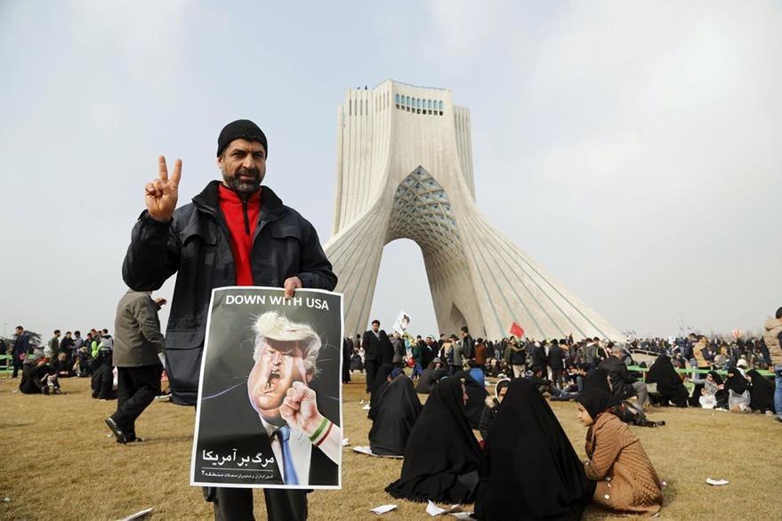 Un iraní hace el signo de la victoria mientras enseña un cartel contra Trump. (EFE).