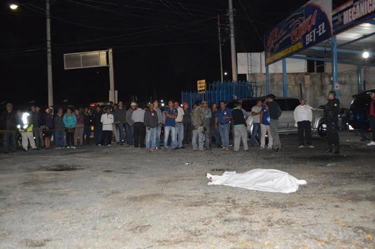 Curiosos se reúnen en el área donde fue ultimado Joel Recinos Martínez, en la ciudad de Huehuetenango. (Foto Prensa Libre: Mike Castillo).