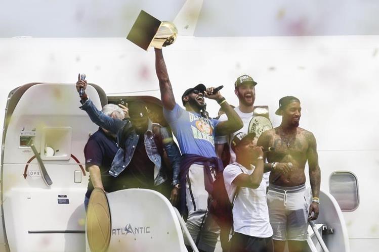 LeBron James desciende del avión con el trofeo de campeón, tras su arribo a Cleveland. (Foto Prensa Libre: AP).