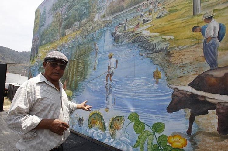 Pintor Carlos Sacú hace alusión al mural de la feria que recuerda cómo era el río Michatoya entre los años 50 y 70. (Foto Prensa Libre: Paulo Raquec).