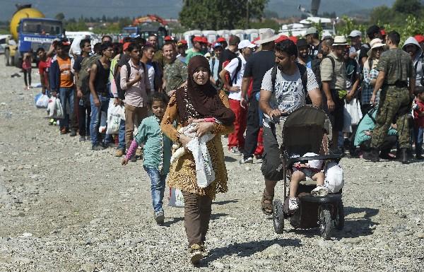 <em>Un grupo de inmigrantes se disponen a subir a un tren en Gevgelija, Macedonia.</em>