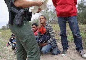 Un agente de la Patrulla Fronteriza de EE. UU. revisa los documentos de un grupo de inmigrantes centroamericanos en McAllen, Texas. (Foto Prensa Libre: AFP).