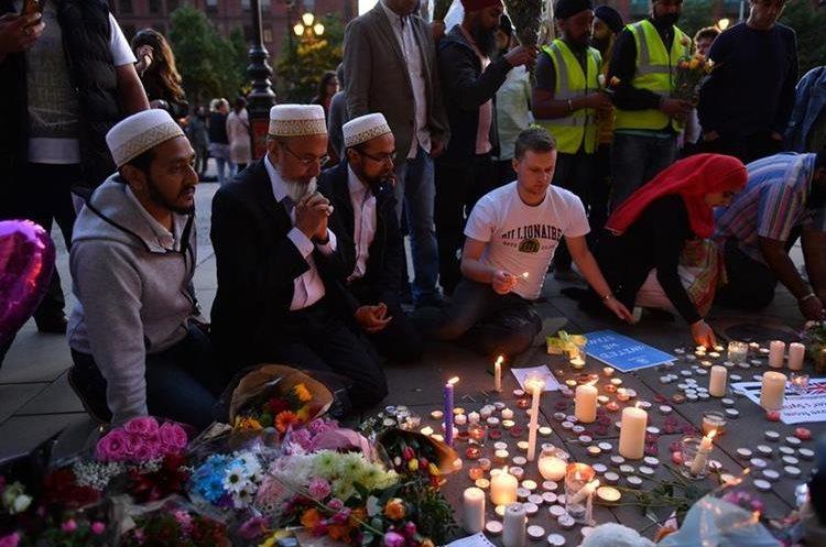 Varias personas ora y enciende velas  en solidaridad con las víctimas del ataque. (AFP).