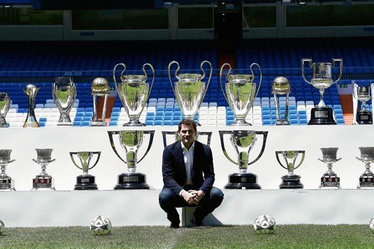 Iker Casillas posa en el estadio Santiago Bernabéu co los trofeos que ganó con el Real Madrid. (Foto Prensa Libre: AFP)