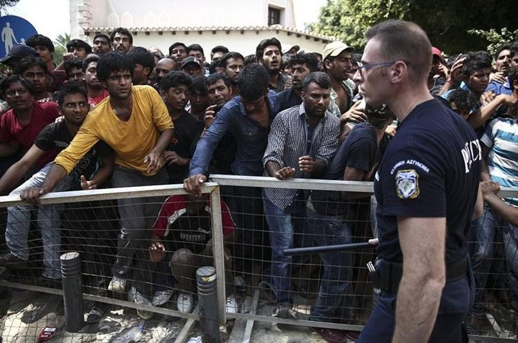 Migrants wait behind a fence for a registration procedure outside a police station at southeastern island of Kos, Monday, Aug. 10, 2015.  Greece