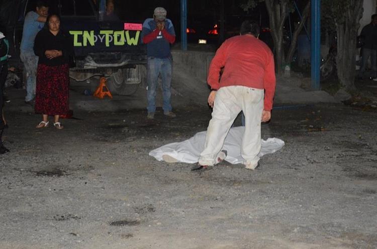 Curiosos observan el cadáver de Joel Recinos Martínez, quien fue ultimado en Huehuetenango. (Foto Prensa Libre: Mike Castillo).