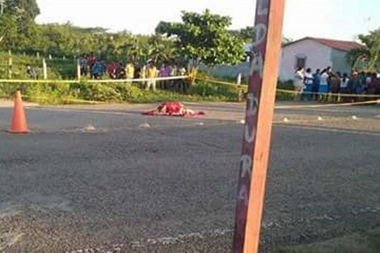 Vecinos observan el cadáver de la maestra Anita Consuelo Guardado Tesucún, en el área conocida como Cruce de El Ceibo, San Andrés. (Foto Prensa Libre: Rigoberto Escobar)