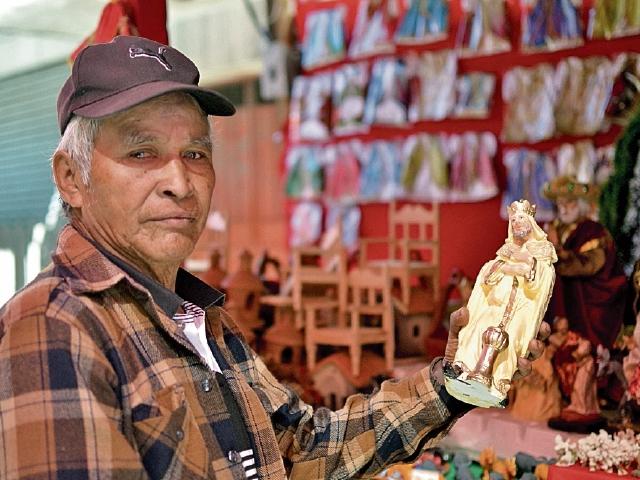"""A sus 65 años,  JulioCésar Itz lleva 55 años de tener su negocio navideño. """"Vine de Cobán hace  60 años y comencé con los negocios. Actualmente hay mucha competencia y no se vende igual que antes"""", dice mientras limpia con cuidado una de  las figuras de los reyes magos."""