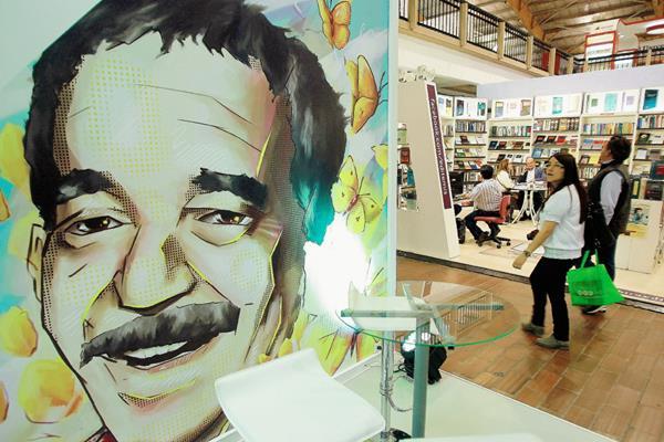 Una pareja pasa frente a una ilustración del nobel colombiano Gabriel García Márquez, en la 28 edición de la Feria Internacional del Libro de Bogotá (Colombia).