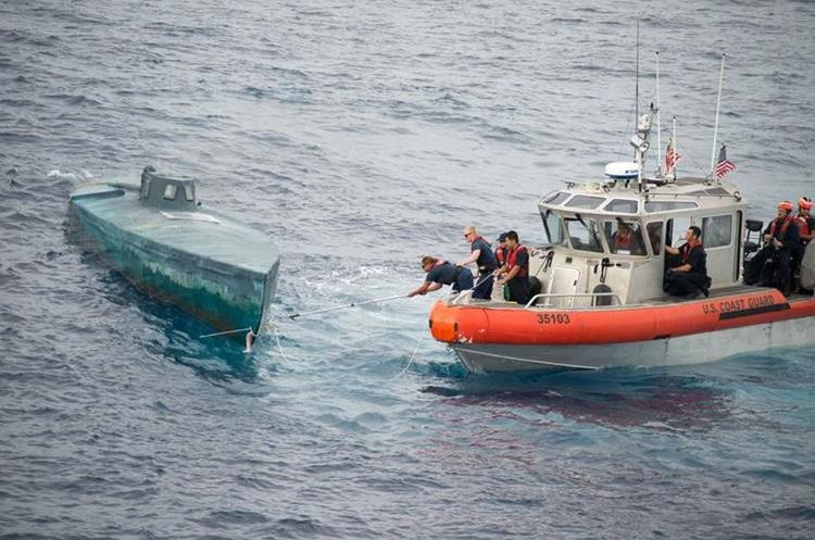 """In this image obtained from the US Coast Guard on August 6, 2015, crew from the Coast Guard Cutter Stratton intercept a self-Propelled Semi Submersible in the Eastern Pacific, on July 18, 2015. The US Coast Guard said it seized $181 million worth of cocaine from a submarine-like vessel in the eastern Pacific Ocean, but even more drugs sank during the bust. The Coast Guard seized 12,000 pounds (5,400 kilograms) of cocaine from four smugglers on a semi-submersible ship, the agency said August 6. The vessel, which was first spotted about 200 miles (320 kilometers) south of Mexico, was carrying a total of 16,000 pounds of narcotics, but as the ship was being towed, it took on water and sank. Some 4,000 pounds of narcotics were lost in the process.    == RESTRICTED TO EDITORIAL USE / MANDATORY CREDIT: """"AFP PHOTO HANDOUT-US COAST GUARD/Petty Officer 2nd Class LaNola Stone""""/ NO MARKETING - NO ADVERTISING CAMPAIGNS – NO A LA CARTE SALES / DISTRIBUTED AS A SERVICE TO CLIENTS =="""