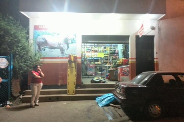 Los cuerpos de la pareja quedaron frente a la tienda en donde fueron atacados. (Foto Prensa Libre: Estuardo Paredes)