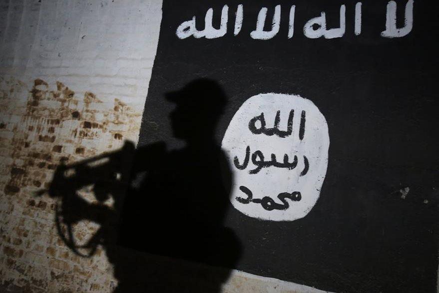 Un miembro de las fuerzas gubernamentales camina frente a una bandera que identifica al grupo terrorista Estado Islámico. (Foto Prensa Libre: AFP)