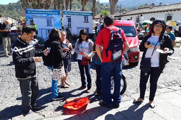 Voluntarios ofrecen los últimos números para la rifa un millón amigos. (Foto Prensa Libre: Julio Sicán)