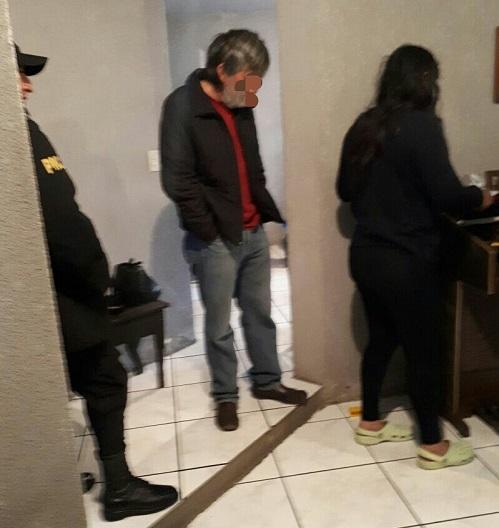 Uno de los detenidos sindicado de lavado de dinero, durante el momento de su captura. (Foto Prensa Libre: PNC)
