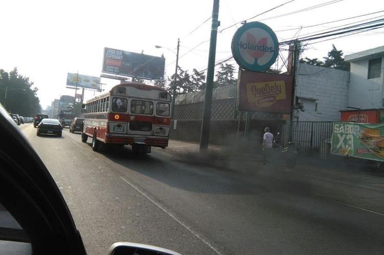 Una persona camina en medio de una nube de humo producida por un bus urbano, en la Calzada Roosevelt, Mixco. (Foto Prensa Libre: César Pérez)