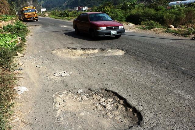 Pilotos que utilizan la ruta de Retalhuleu a Quetzaltenango deben esquivar la gran cantidad de hoyos que hay en carretera, lo que ha causado accidentes. Alrededor de 100 personas han muerto desde el 2005, según cuerpos de socorro. (Foto Prensa Libre: Carlos Ventura)