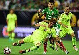 El venezolano Adalberto Penaranda izquierda supera al mexicano Jesus Molina, durante el partido que terminó empatado 1-1. (Foto Prensa Libre: AFP)