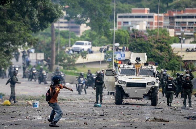 Manifestantes se enfrentan a la Policía este miércoles en Caracas. Foto Prensa Libre: AFP.