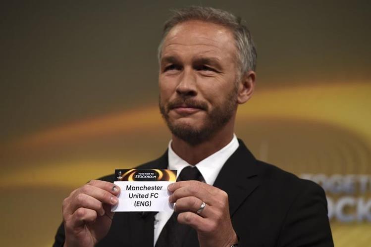 Patrik Andersson, embajador de la UEFA, muestra el nombre del Manchester United en el sorteo de los octavos de final. (Foto Prensa Libre: AFP)