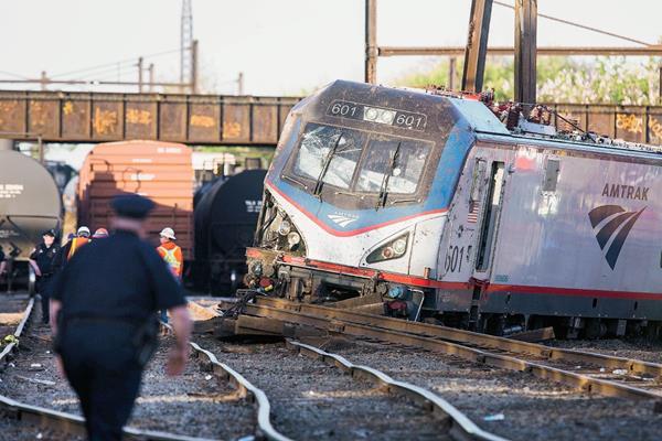 Operarios trabajan en el lugar donde un tren ha descarrilado en Filadelfia, Estados Unidos, (Foto Prensa Libre:EFE).