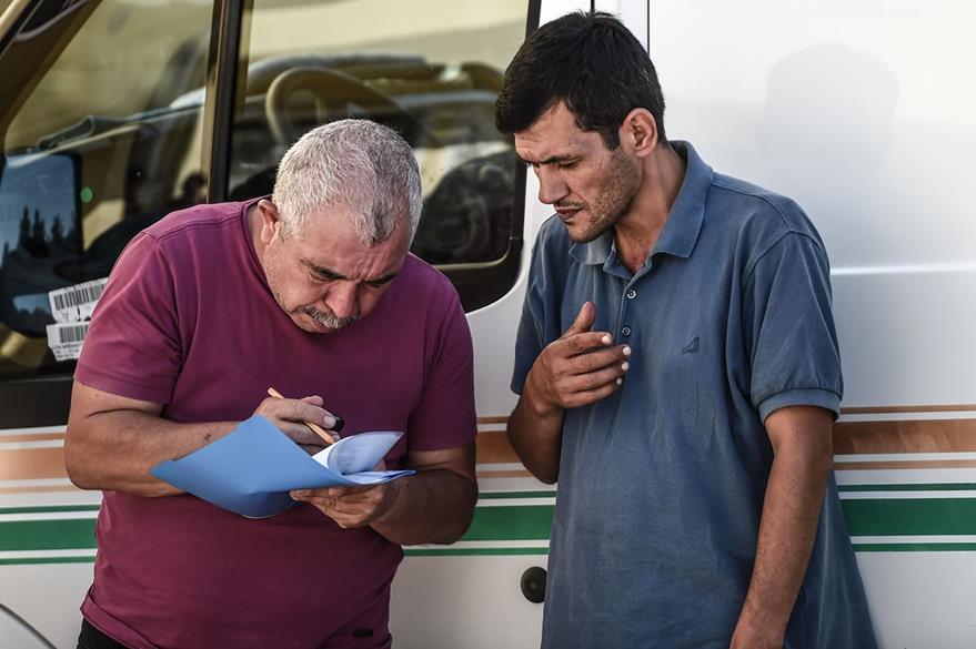 Abdullah Kurdi (derecha), ofrece información a las autoridades migratorias turcas. (Foto Prensa Libre: AFP).