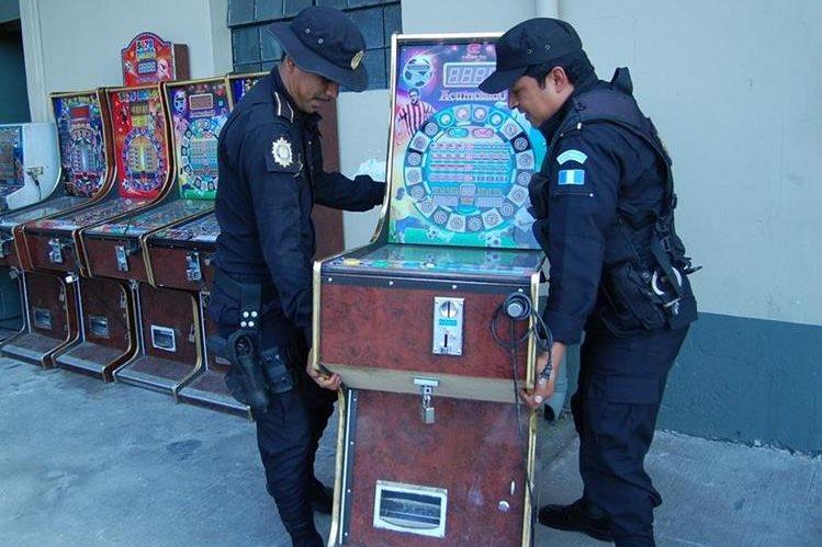 Agentes de la PNC cargan uno de los 19 aparatos decomisados. (Fotos Prensa Libre: Víctor Chamalé).