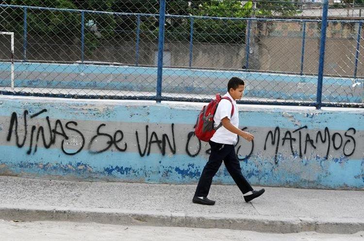 Un estudiante pasa frente a un graffiti hecho por la pandilla Mara Salvatrucha en el barrio El Bosque. (Foto Prensa Libre:AFP).