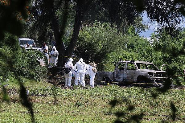 Forenses trabajan en el sitio donde nueve personas fueron encontradas carbonizadas.