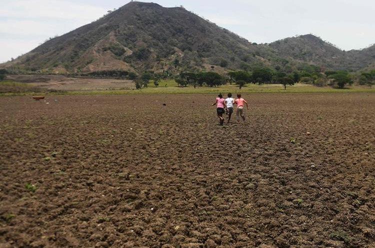 Un grupo de niños corre sobre el terreno árido de lo que en algún momento fue la Laguna de Atescatempa, Jutiapa. (Foto Prensa Libre: AFP)