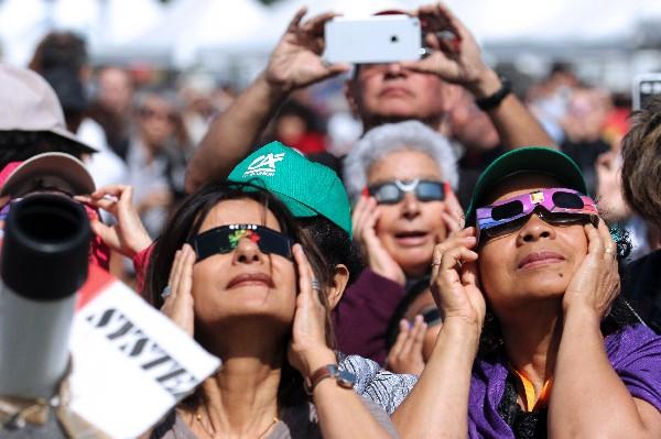 Varias personas observa el eclipse en la isla La Reunión del océano Índico.(AFP).