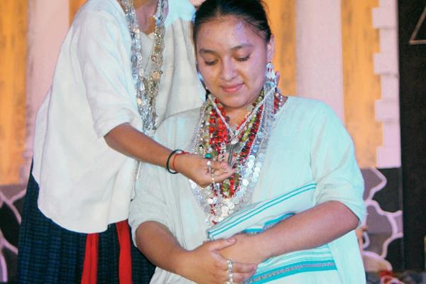 Gladis Elizabeth Tiul Rax, reina saliente, coloca la Cruz del Cristo Yacente de la Agonía a la ganadora Yésica Eloíza Hun Chen. (Foto Prensa Libre: Ángel Tax)