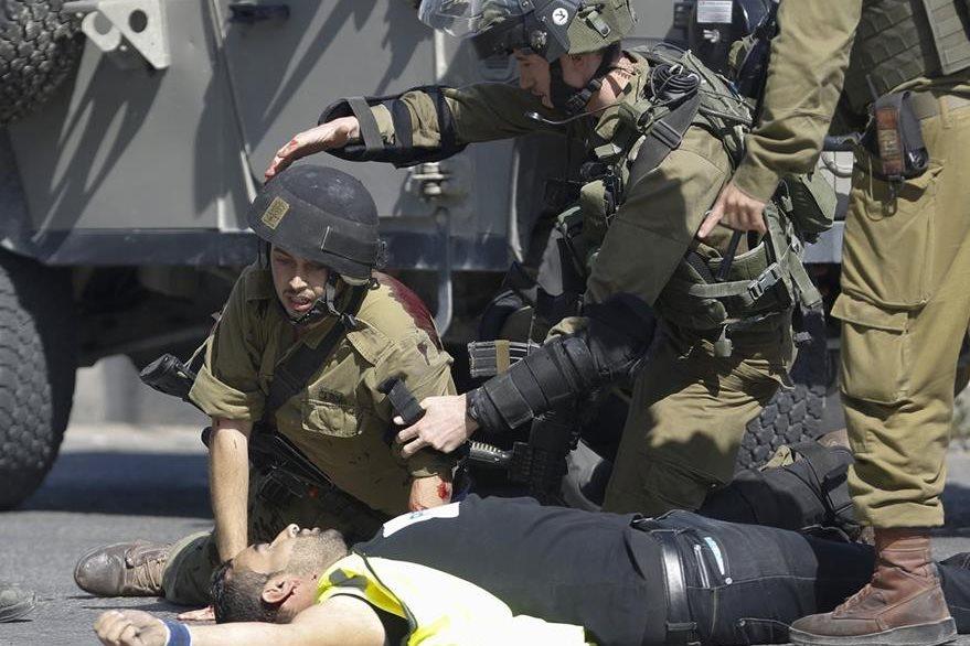 """Un soldado herido permanece de rodillas sobre el cuerpo del palestino muerto que lo atacó y que portaba un chaleco amarillo en donde se leía """"Prensa"""". (Foto Prensa Libre: AP)."""
