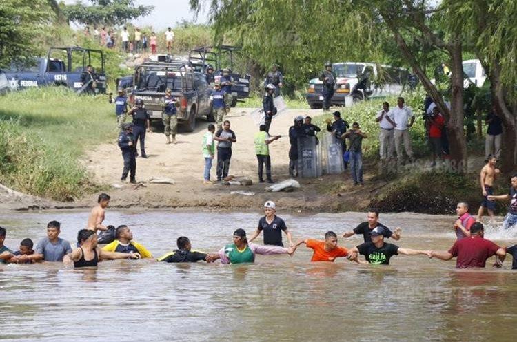 Migrantes hondureños atraviesan el río Suchiate.