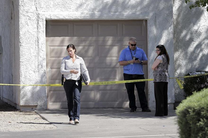 Oficiales vigilan en las afueras de la vivienda de Phoenix donde una madre asesinó a sus tres hijos e intentó suicidarse. (Foto Prensa Libre: AP).