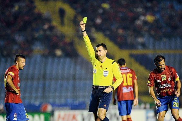Mario Escobar le muestra una tarjeta amarilla a un jugador de Municipal, en el encuentro contra los cremas, en el clásico 287 (Foto Prensa Libre: Francisco Sánchez)