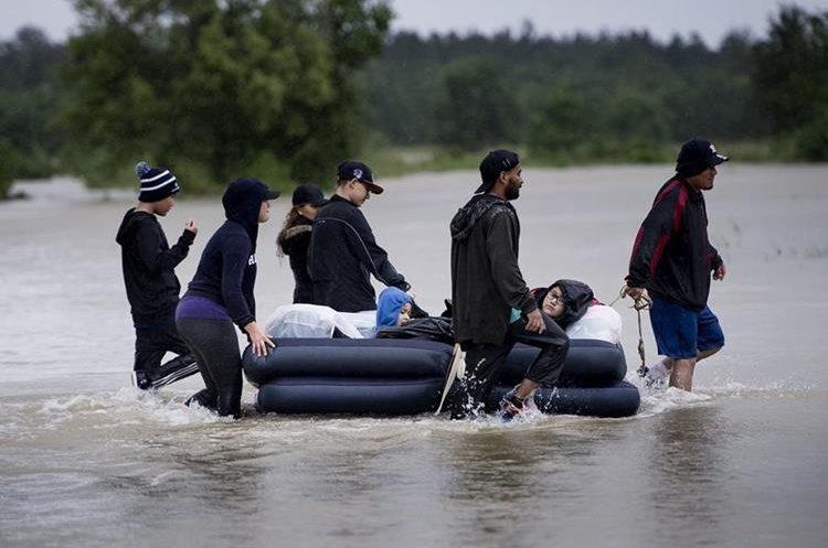 Varios pobladores escapan de un vecindario inundado usando un colchón inflable en Houston, Texas.(AFP).