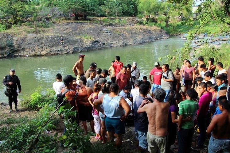 Vecinos y familiares llegan a identificar el cuerpo de Wilmer Elías López, de 17 años, a orillas del río Ocosito. (Foto Prensa Libre: Rolando Miranda)