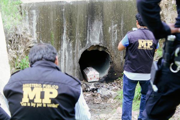 Fiscales del Ministerio Público recogen evidencias en el lugar en el que fue hallado un féretro con los restos de un bebé. (Foto Prensa Libre: Hugo Oliva)