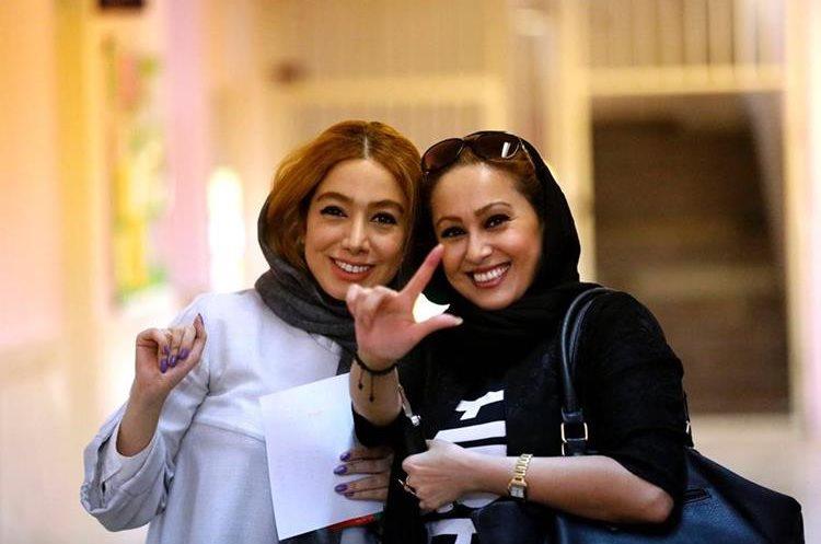 Damas iraníes muestran su dedo con tinta después de votar.