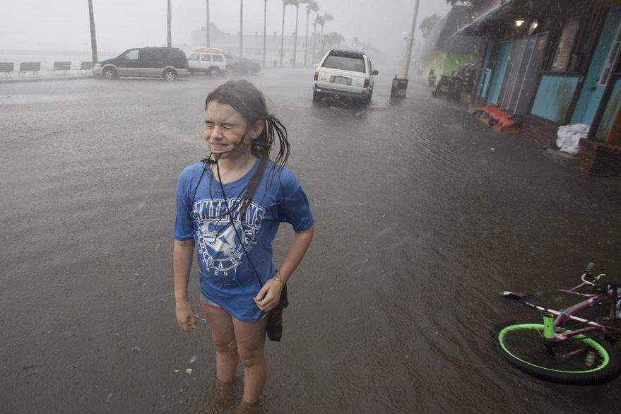 Una niña juega con el agua en una localidad de Florida que ya experimenta fuertes lluvias. (Foto Prensa Libre: AP).