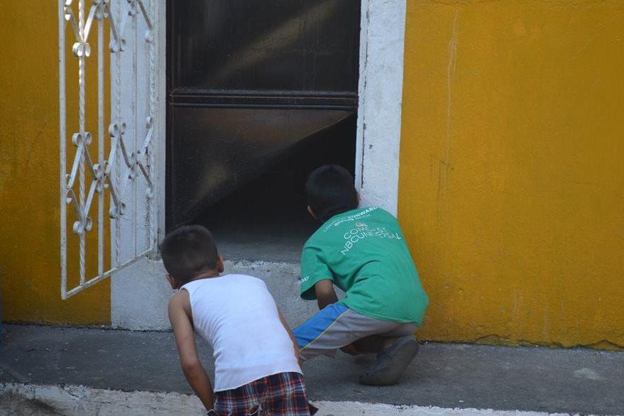Niños observan la puerta de la bodega que fue forzada por los malhechores.(Foto Prensa Libre: Jorge Tizol)