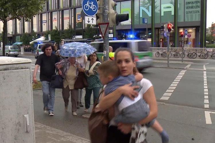 Un mujer huye con su bebé del centro comercial donde se produjo la balacera en Múnich. (Foto Prensa Libre: AP).