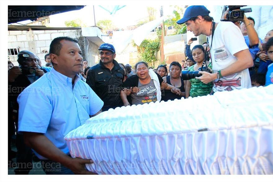 Empleado de funeraria entrega los cuerpos de las víctimas de envenenamiento. (Foto: Hemeroteca PL)