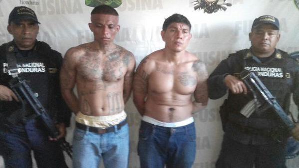 Policías custodian a los dos pandilleros recapturados en Honduras. (Foto: Prensa Libre/Fiscalía General de El Salvador).