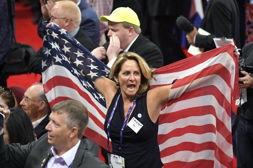 Una delegada republicana grita con una bandera de los Estados Unidos, durante la inauguración de la convención. (Foto Prensa Libre: AP).