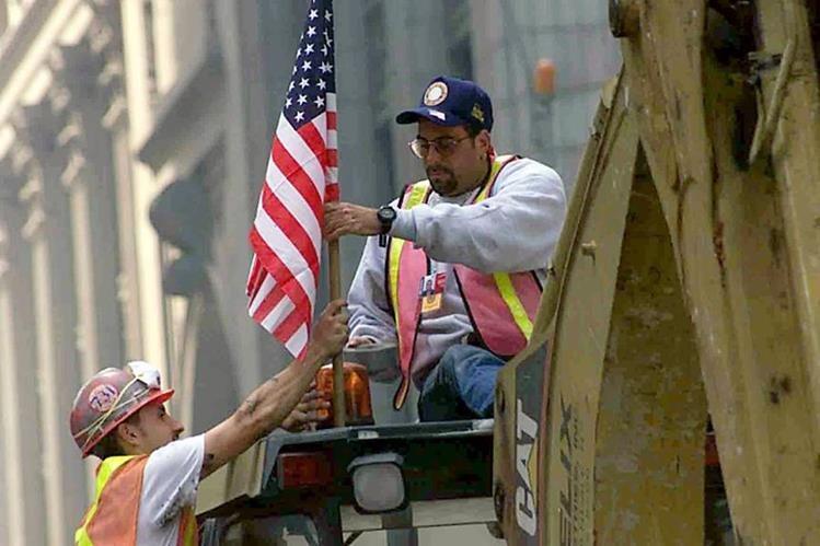 Rescatistas colocan una bandera de EE. UU. antes de comenzar los trabajos aquel fatídico 11 de septiembre del 2001. (Foto Hemeroteca PL).
