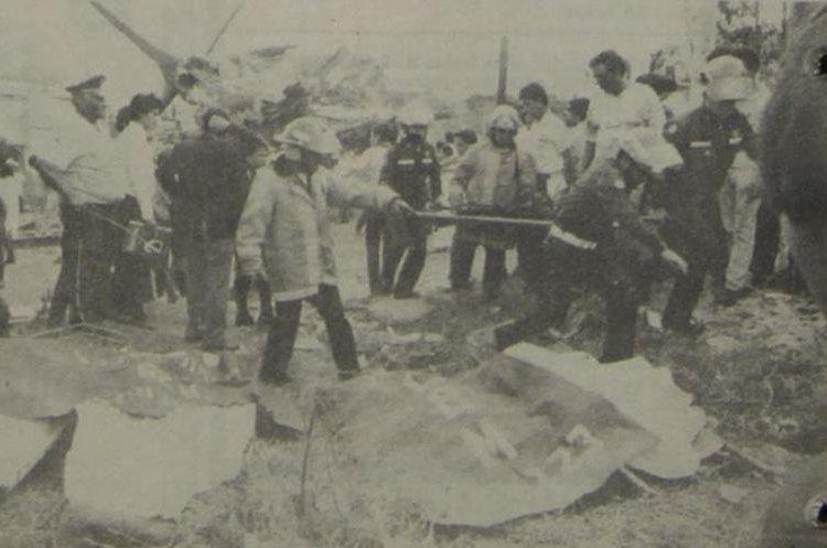 Los bomberos colocan varios cadáveres en un terreno baldío situado frente al lugar donde cayó el avión, el cual se observa al fondo, destruido. 5/5/1990. (Foto: Hemeroteca PL)